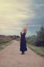 woman standing on a dirt road with hand raised praising God