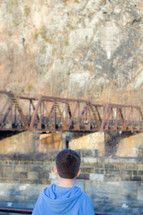 a child looking at an old rusty train bridge
