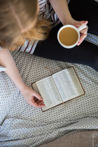 a girl sitting on a bed with coffee reading a Bible