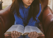 A young woman sitting in a chair reading her Bible