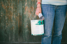 Person from waist down, holding a paint can and paint brush, standing in front of a green wooded wall