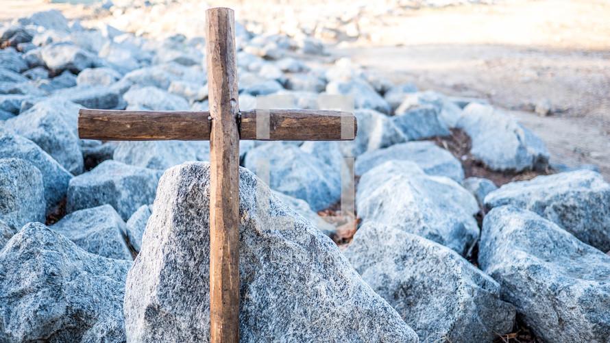 wooden cross on rocks