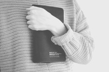 a woman holding a Bible against her chest