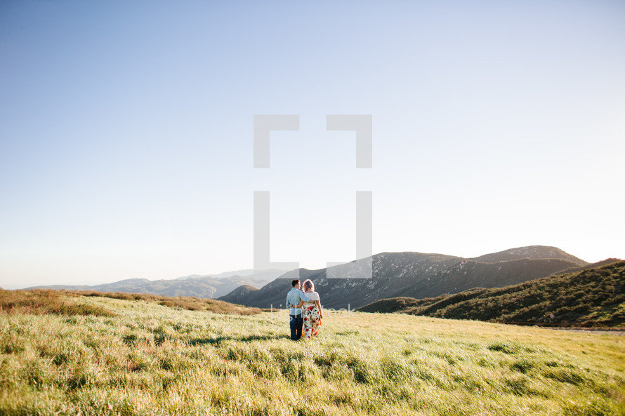 a couple walking holding each other on a mountaintop at sunset