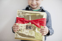 A child holding a gift for dad