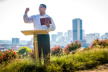 a man standing at a podium reading a Bible outdoors