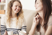 Smiling friends enjoying coffee together while sitting on the sofa.