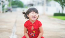 Happy Little asian girl in chinese traditional dress laughing and smiling