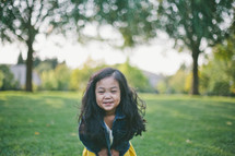 A smiling little girl in a field of grass.