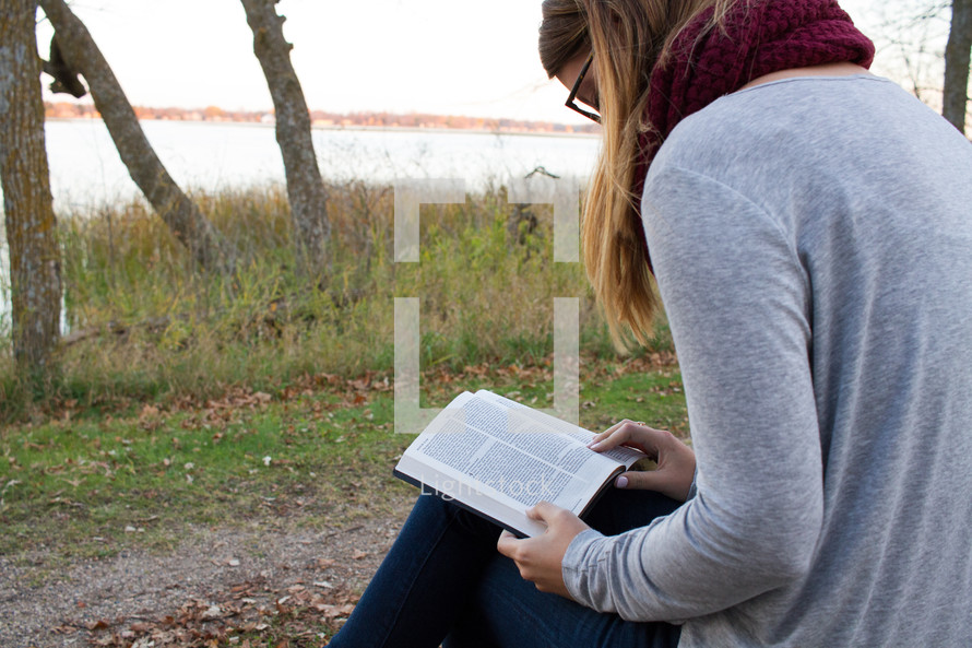 a woman sitting outdoors in fall reading a Bible
