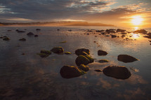 rocks in water at sunset