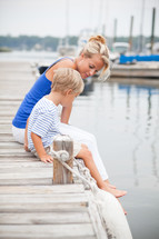 mother and son sitting at the edge of a dock