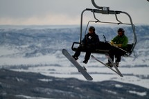 snow boarder and skier on a ski lift chair