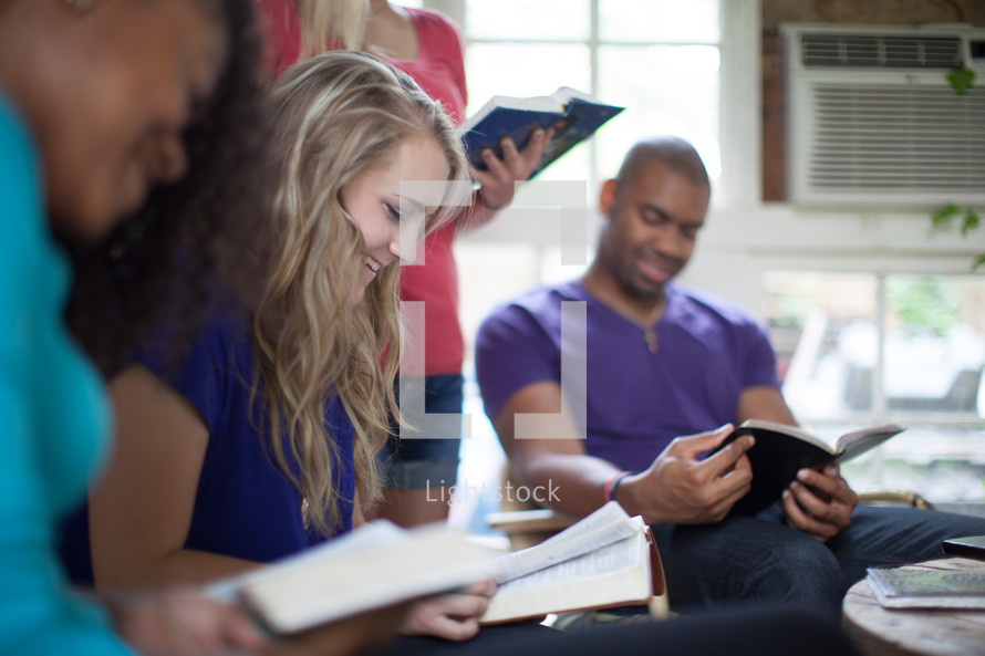 reading Bibles and smiling at a Bible study