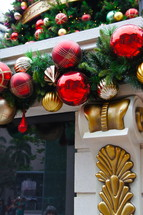 Fireplace mantle with gold and red ball ornaments and pine needles hanging from it.