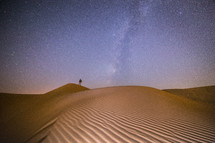 standing on sand dunes under a starry sky