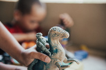 child playing with a dinosaur toy