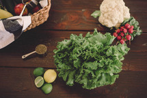 lettuce, lemons, limes, radishes, cauliflower and other vegetables in a basket