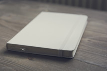 Blank Moleskine Notebook. Closed white notebook on a wooden table.