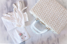 White gloves, handkerchief, and straw handbag on a marble table