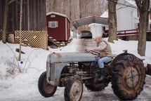 an elderly man on a tractor in winter
