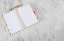 Blank pages in a diary with pen on a marble table