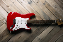 a red electric guitar on a wooden table.