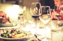 salad and wine glasses at a dinner party