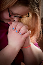 a teen girl with head bowed in prayer