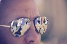 reflection of a crowd of people in a man's sunglasses