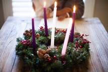 mother and son reading a Bible in front of an Advent wreath