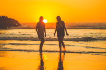 young women walking on a beach at sunset