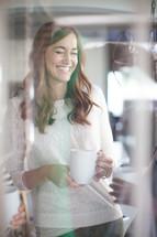 a smiling woman holding a coffee mug