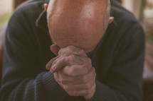 Man praying with his head on his hands.