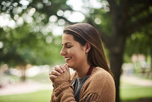 a woman with praying hands standing outdoors in fall