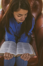 A woman sitting reading a Bible