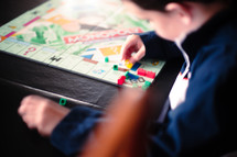 A boy plays with game pieces on a board game.