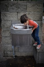 a little girl drinking from a water fountain