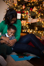 mother and son reading a Christmas story near a Christmas tree