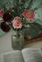 vase with red and pink flowers and an opened Bible