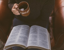 A woman reading the Bible and holding a coffee mug