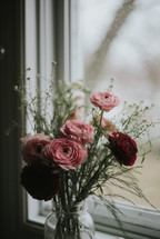 vase of pink and red flowers in a window