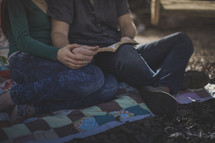 A man and woman sitting on a blanket reading the Bible together
