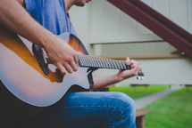 Hands playing a guitar outside.
