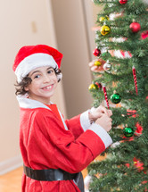 A little boy wearing a Santa hat decorating a Christmas tree.