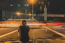 a man sitting on a city curb at night