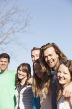 Group of joyful friends standing outside.