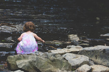 toddler girl playing by the edge of a stream