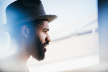 side profile of a man in a hat with a beard