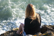 woman sitting on rocks along a shore writing in a journal
